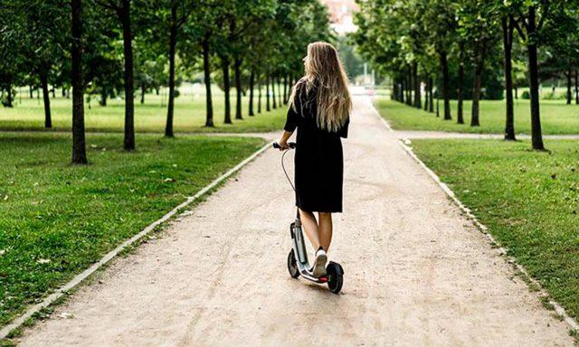 Foto de una chica subida en un patinete eléctrico